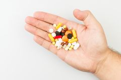 Pills in male hand on the medical table. Many pills in male hand on the medical table Stock Photos