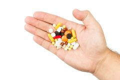 Pills in male hand on white background. Pills in male hand on isolated white background Stock Image
