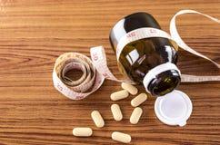 Pills and measuring tape Stock Photos