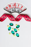 Pills with measuring tape on white scales Stock Photo
