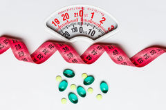 Pills with measuring tape on white scales Royalty Free Stock Photography