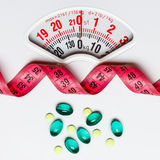 Pills with measuring tape on white scales Stock Photography