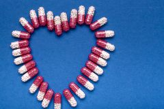 Pills medical background heart shape a over blue background stock image