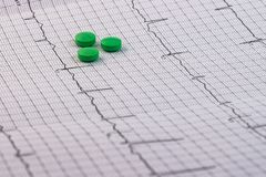 Pills and medicines of green color on an electrocardiogram stock images