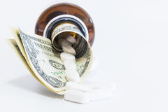 Pills and Money on white background Royalty Free Stock Images