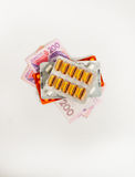 Pills on money on a white background Stock Photos
