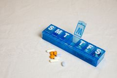 Pills next to weekly dispenser. Assorted pills next to blue plastic pill weekly organizer on white Stock Photo