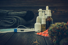 Pills, nose drops a cold treatment, flu runny on the table with an electronic thermometer, toned image Stock Image