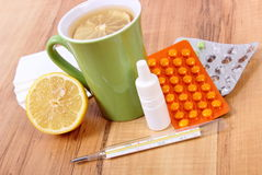 Pills and nose drops for colds, handkerchiefs and hot tea with lemon Royalty Free Stock Photography