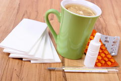 Pills and nose drops for colds, handkerchiefs and hot tea with lemon Royalty Free Stock Image