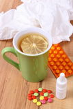 Pills and nose drops for colds, handkerchiefs and hot tea with lemon Stock Images