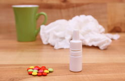 Pills and nose drops for colds, used handkerchiefs and hot tea Royalty Free Stock Photo