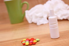 Pills and nose drops for colds, used handkerchiefs and hot tea Royalty Free Stock Photography