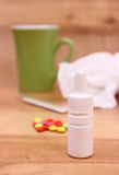 Pills and nose drops for colds, used handkerchiefs and hot tea Stock Photography