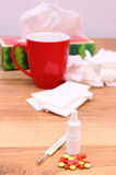 Pills and nose drops for colds, used handkerchiefs and hot tea with lemon Stock Photo