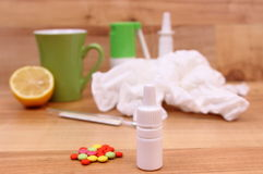 Pills and nose drops for colds, used handkerchiefs and hot tea with lemon Royalty Free Stock Photography
