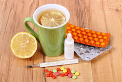 Pills, nose drops and hot tea with lemon for colds, treatment of flu and runny Royalty Free Stock Photo