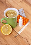 Pills, nose drops and hot tea with lemon for colds, treatment of flu and runny Stock Photography