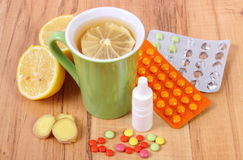 Pills, nose drops and hot tea with lemon for colds, treatment of flu and runny Royalty Free Stock Photos