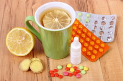 Pills, nose drops and hot tea with lemon for colds, treatment of flu and runny Stock Image