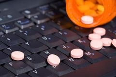 Pills on notebook keyboard. Notebook keyboard covered by pills pouring out of a prescription bottle royalty free stock photography