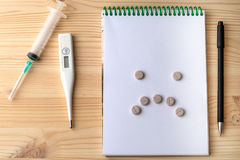 Pills on a Notepad on a wooden table. In the form of sad faces Royalty Free Stock Photo