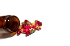 Pills and opened bottle. A close-up of colourful pills poured out of medicine bottle royalty free stock image