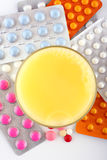 Pills and orange soda. Medicine pills and orange juice stock photo