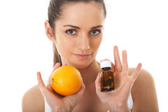 Pills or orange, two sources of vitamins, isolated Stock Images