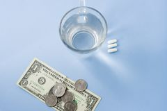 Pills organized next to a cup of water with one dollar and coins royalty free stock image