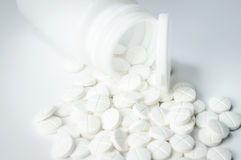 Pills out of bottle. White pills out of pill bottle Stock Photos