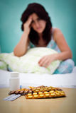 Pills and out of focus sick or depressed woman Royalty Free Stock Photo