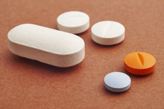 Pills over a brown background. Medicament treatment. Health care. Photo Stock Images