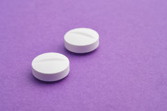 Pills over a purple background. Medicament treatment. Health car Stock Photography