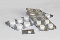 Pills in package lying white table. Pills in a package lying on a white table stock images