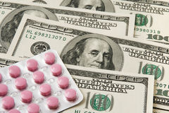 Pills package on money background. Package of pink pills on US money background Royalty Free Stock Photo