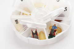 Pills and pensioner´s figurine in pill organiser, close up Stock Image
