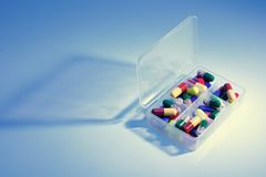 Pills in Pill Box. In Blue Cast Stock Image