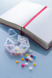Pills planner with weekly medication capsules and note book Stock Image