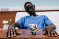 Pills in plastic glass. Selective focus of pills in plastic glass and african american man lying in hospital bed Stock Images