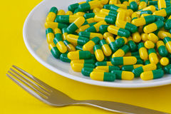 Pills on a plate. Green yellow capsule Pills on a white plate with Fork Stock Photos