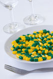 Pills on a plate. Green and yellow capsule Pills on a white plate with fork Stock Photos