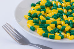 Pills on a plate. Green and yellow capsule Pills on a white plate with fork Royalty Free Stock Images