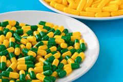 Pills on a plate. Green and yellow capsule pills on a white plate Stock Photos