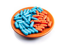Pills on the plate. Blue and orange pills on the plate isolated on white Stock Images