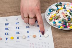 Pills in plate on calendar. Close up Stock Photo