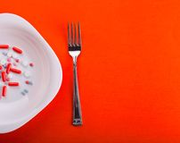 Pills on plate with fork. Many colorful pills on white  plate with steel fork Stock Photos