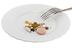 Pills on a plate with a fork. Isolated Stock Photos