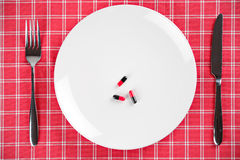 Pills on a plate with fork and knife. Pills on a white plate with fork and knife Stock Photography