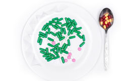 Pills are on plate next to spoon with dose Stock Image